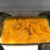 peaches about to go in the oven, with the melted butter in the bottom of the dish